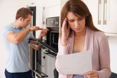 Kvinna som ser oroad på kostnad av reparationen Bill For Domestic Applia arkivfoton