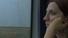 Kvinna som ser på regnigt drevfönster stock video
