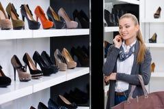 Kvinna som ser raderna av skodon royaltyfri bild