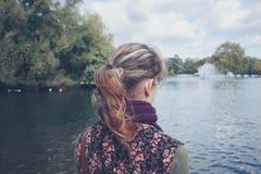 Kvinna som ser sjön i en parkera Arkivbilder