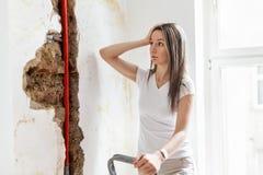 Kvinna som ser skada efter en läcka för vattenrör arkivfoton