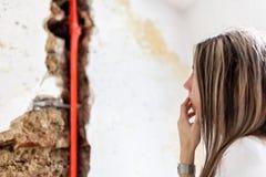 Kvinna som ser skada efter en läcka för vattenrör royaltyfri foto