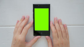 Kvinna som ser smartphonen med den gröna skärmen Royaltyfri Bild