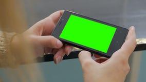 Kvinna som ser smartphonen med den gröna skärmen Royaltyfri Foto