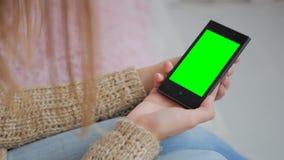 Kvinna som ser smartphonen med den gröna skärmen Royaltyfri Fotografi