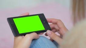 Kvinna som ser smartphonen med den gröna skärmen Royaltyfria Foton