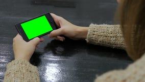 Kvinna som ser smartphonen med den gröna skärmen Fotografering för Bildbyråer