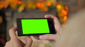 Kvinna som ser smartphonen med den gröna skärmen Arkivfoto