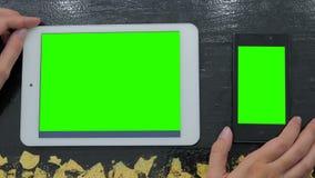 Kvinna som ser smartphonen och den digitala minnestavlan med den gröna skärmen Royaltyfria Foton