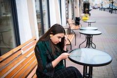 Kvinna som ser smartphonen på rubbningen för gatakafékänsla royaltyfri bild