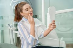 Kvinna som ser spegeln och tycker om leende i tand- kontor royaltyfri foto
