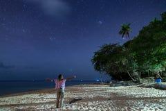 Kvinna som ser stj?rnor och den mj?lkaktiga v?gen p? sandstranden, facklaljus p? natthimmel, bakre sikt, verkligt folk Indonesien arkivbilder