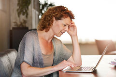 Kvinna som ser tänkande sammanträde för dator på tabellen Royaltyfri Foto