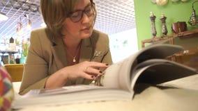 Kvinna som ser tidskriftsidor lager videofilmer