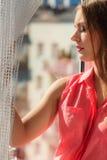 Kvinna som ser till och med fönstret som kopplar av Arkivbilder