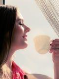 Kvinna som ser till och med fönstret som kopplar av dricka kaffe Royaltyfri Fotografi