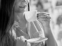 Kvinna som ser till och med fönstret som kopplar av dricka kaffe Arkivbilder