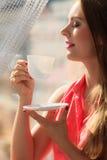 Kvinna som ser till och med fönstret som kopplar av dricka kaffe Arkivbild