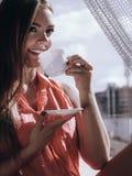 Kvinna som ser till och med fönstret som kopplar av dricka kaffe Royaltyfria Bilder