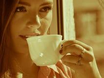 Kvinna som ser till och med fönstret som kopplar av dricka kaffe Arkivfoto