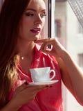 Kvinna som ser till och med fönstret som kopplar av dricka kaffe Arkivfoton