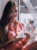 Kvinna som ser till och med fönstret som kopplar av dricka kaffe Royaltyfri Foto