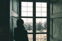 Kvinna som ser till och med fönstret, tonad bild, tappningstil Turin cityscape, Torino, Italien, gammalt hus, bakre sikt i skugga royaltyfri fotografi
