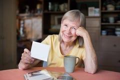 Kvinna som ser till och med foto i bildalbum arkivfoton