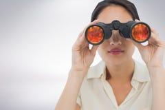 Kvinna som ser till och med kikare mot vit bakgrund arkivfoto