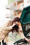 Kvinna som ser under bilhuven på telefonen Royaltyfri Bild