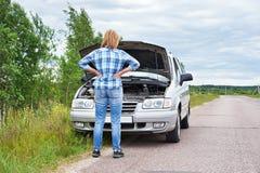 Kvinna som ser under huven av den brutna bilen Arkivfoton