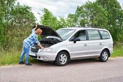 Kvinna som ser under huven av den brutna bilen Fotografering för Bildbyråer