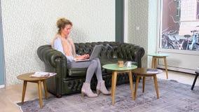 Kvinna som ser vännen som använder mobiltelefonen i kafé lager videofilmer