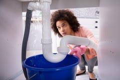 Kvinna som ser vatten som l?cker fr?n vaskr?ret arkivbild