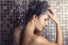 Kvinna som shampooing hennes långa bruna hår Royaltyfri Bild