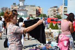 Kvinna som shoppar andrahands- kläder på en loppmarknad Royaltyfria Bilder