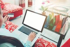 Kvinna som shoppar direktanslutet genom att använda bärbara datorn med den tomma skärmen, krediteringsbil Royaltyfri Fotografi