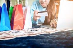 Kvinna som shoppar direktanslutet genom att använda bärbara datorn med kreditkorten som in tycker om Royaltyfria Bilder