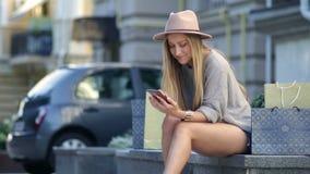 Kvinna som shoppar direktanslutet genom att använda den utomhus- mobiltelefonen