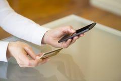 Kvinna som shoppar direktanslutet genom att använda mobiltelefonen och kreditkorten inomhus Arkivbild