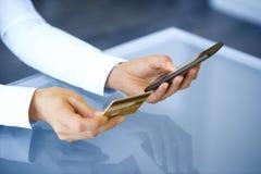 Kvinna som shoppar direktanslutet genom att använda mobiltelefonen och kreditkorten inomhus Arkivfoto