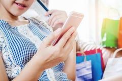 Kvinna som shoppar direktanslutet genom att använda smartphonen med att tycka om för kreditkort Arkivfoton