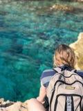 Kvinna som sitter över havet i Cypern royaltyfria bilder