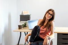 Kvinna som sitter det hemmastadda skrivbordet Royaltyfri Fotografi