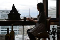 Kvinna som sitter i franskt stilrum i Paris, bakgrund Eiffeltorn, Frankrike royaltyfri bild