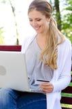 Kvinna som sitter i park och online shoppar Arkivbild