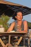 Kvinna som sitter i utomhus- cafe Arkivfoto