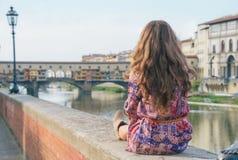 Kvinna som sitter nära pontevecchio i florence Fotografering för Bildbyråer