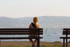 Kvinna som sitter på bänk Royaltyfria Foton