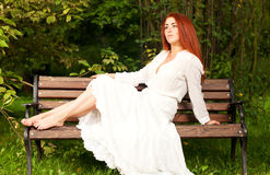 Kvinna som sitter på bänk royaltyfri foto
